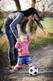 kleines Mädchen und Mutter mit einem Ball Stockbilder