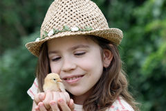 Kleines Mädchen und nettes gelbes Huhn stockfoto