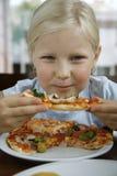 Kleines Mädchen und Pizza Lizenzfreie Stockbilder