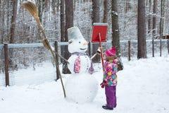 Kleines Mädchen und Schneemann Stockbilder