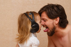 Kleines Mädchen und Vati hört Musik Stockbilder