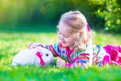 Kleines Mädchen und wirkliches Kaninchen stockfoto