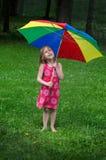 Kleines Mädchen unter buntem Regenschirm Stockbild