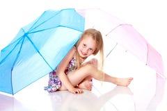 Kleines Mädchen unter einem Regenschirm Stockfotos