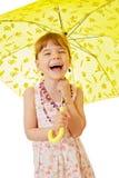 Kleines Mädchen unter gelbem Regenschirm Stockfoto