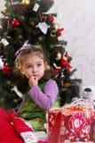 Kleines Mädchen unter Weihnachtsbaum mit Geschenken lizenzfreie stockfotografie