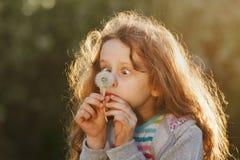 Kleines Mädchen vertraut mähenden Blicken nicht an einem Löwenzahn stockfoto