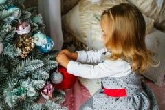 Kleines Mädchen verziert die Weihnachtsbaumspielwaren Lizenzfreie Stockfotografie