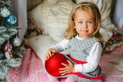 Kleines Mädchen verziert die Weihnachtsbaumspielwaren Stockfotografie