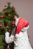 Kleines Mädchen verziert Weihnachtsbaum mit rotem Ball Lizenzfreie Stockbilder