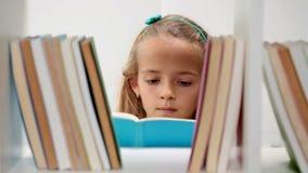 Kleines Mädchen vor Bücherregal stock footage