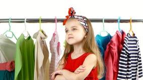 Kleines Mädchen wählt im Geschäft zu sich Kleidung Weißer Hintergrund stock footage