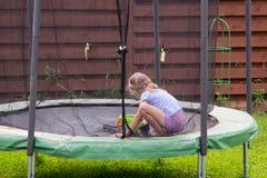Kleines Mädchen wäscht ihre Trampoline im Hinterhof Stockbild