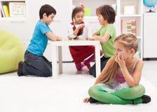 Kleines Mädchen, welches auseinander - das Gefühl ausgeschlossen durch die anderen sitzt stockfoto