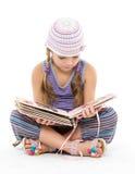 Kleines Mädchen, welches das Album sitzt auf dem Boden schaut Stockbilder