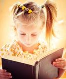 Kleines Mädchen, welches das Buch liest Stockfotografie