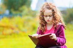 Kleines Mädchen, welches das Buch liest getrennte alte Bücher Lizenzfreies Stockbild