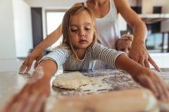 Kleines Mädchen, welches das Kochen und das Backen lernt lizenzfreie stockbilder