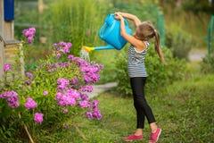 Kleines Mädchen, welches die Blumen nahe dem Landhaus wässert liebhaberei lizenzfreie stockfotografie