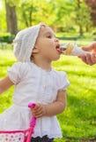 Kleines Mädchen, welches die Eiscreme im Freien isst Lizenzfreie Stockfotos