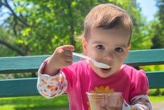 Kleines Mädchen, welches die Eiscreme im Freien isst Lizenzfreie Stockbilder