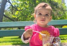 Kleines Mädchen, welches die Eiscreme im Freien isst Stockbilder