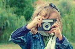Kleines Mädchen, welches die Fotos im Freien macht Stockfotografie