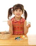 Kleines Mädchen, welches die Ostereier malt Lizenzfreie Stockbilder