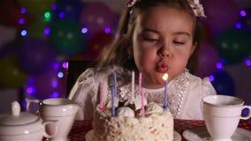 Kleines Mädchen, welches heraus die Kerzen des Geburtstagskuchens durchbrennt stock video footage