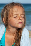 Kleines Mädchen, welches oben die Sonne auf dem Seeufer tränkt Lizenzfreie Stockfotos