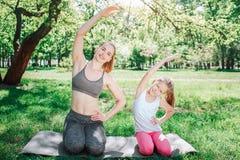 Kleines Mädchen wiederholt ecxercise nach ihrer Mutter Sie halten linke Hand auf Hüften und rechte Hand ist in der Luft stockbild