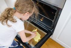 Kleines Mädchen wischt Ofen ab Lizenzfreie Stockfotografie