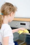 Kleines Mädchen wischt Ofen ab Lizenzfreies Stockbild