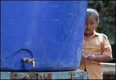 Kleines Mädchen wusch ihre Hand an der vorübergehenden Schule in den Evakuierungs-Kasernen nach Eruption von Merapi-Berg lizenzfreie stockbilder