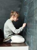 Kleines Mädchen zeichnet auf eine Tafel lizenzfreies stockfoto