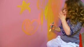 Kleines Mädchen zeichnet auf Wandsterne und -herz stock video footage