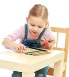 Kleines Mädchen zeichnet die Bleistifte, die am Tisch sitzen Stockfotos