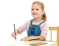 Kleines Mädchen zeichnet die Bleistifte, die am Tisch sitzen Lizenzfreie Stockfotos