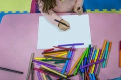 Kleines Mädchen zeichnet in in eine Kind-` s Mitte, einen Garten und eine Schule auf einem weißen Blatt Lizenzfreie Stockbilder