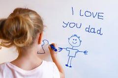 Kleines Mädchen zeichnet Familie mit Markierung auf einem weißen Brett Stockfotos