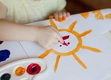 Kleines Mädchen zeichnet Farben die Sonne Lizenzfreies Stockfoto