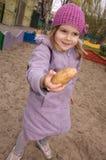 Kleines Mädchen zeigt eine Kartoffel Stockfotografie
