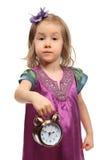 Kleines Mädchen zeigt Zeit auf runder Alarmuhr Lizenzfreie Stockfotos