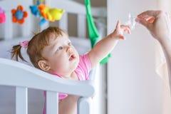 Kleines Mädchen zieht ihre Hand zur Attrappe und steht in einer Babykrippe Lizenzfreie Stockfotografie