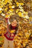Kleines Mädchen zupft Blätter im Herbstpark Lizenzfreies Stockfoto