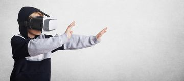 Kleines männliches Kind in den Sweatshirt- und Realitätsgläsern gestikuliert mit den Händen, ausdehnt sie vorwärts, einwirkt auf  Lizenzfreies Stockbild