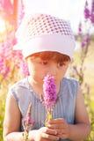 Kleines M?dchen auf einem Gebiet von Blumen stockfotos