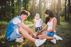 Kleines M?dchen ein Jahr auf dem Hintergrund von den Eltern, die liegend auf dem Gras lernt, auf Natur im Park zu gehen stillsteh stockbild