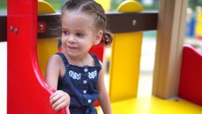 Kleines M?dchen am Spielplatz Kind, das drau?en im Sommer spielt Gl?ckliche Kindheit stock video footage