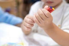 Kleines M?dchen spielt und lernt zu F?rbungszeichenstift auf dem Papier im Eiscremerestaurant , Bangkok, Thailand stockfotos